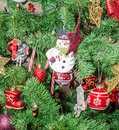 Detail of green christmas chrismas tree with colored ornaments globes stars santa claus snowman red boots shoes candles bells Royalty Free Stock Photography