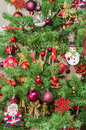 Detail of green Christmas tree with colored ornaments, globes, stars, Santa Claus, Snowman, red boots, shoes, candles Royalty Free Stock Photo