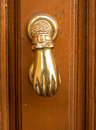 Detail of hand shaped door knocker front view brass like a on old wooden Royalty Free Stock Photography