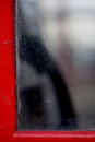Detail of handset seen through window pane of red London phone box Royalty Free Stock Photo