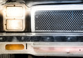 Detail of illuminated headlight and grille of car close up classic with grain added Stock Image