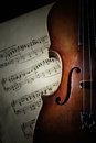 Detail of old scratched violin in shadow music collection on music sheet vintage style Stock Photography
