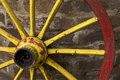 Detail of old wagon wheel with metal rim leaning Royalty Free Stock Photo