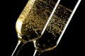 Detail of a pair of flutes of champagne with golden bubbles on black background Royalty Free Stock Image