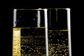 Detail of a pair of flutes of champagne with golden bubbles on black background Royalty Free Stock Images