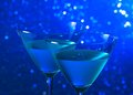 Detail of a pair of glasses of blue cocktail on table tint light bokeh background Stock Images