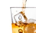 Detail of pouring scotch whiskey in glass with ice cubes on white Royalty Free Stock Photo