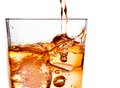 Detail of pouring scotch whiskey in glass with ice cubes on white
