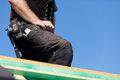 Detail of a roofer standing on roof wearing tool belt Stock Photo