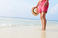 Detail of senior man standing in sea on beach holiday holding a hat Royalty Free Stock Photos