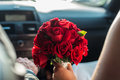 A detail shot of a beautiful bridal bouquet of red roses, held by the bride Royalty Free Stock Photo