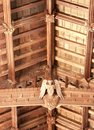 Detail of structure and decoration of wooden medieval church roof interior cross beam decorated with carved figure angel holding a Royalty Free Stock Photos
