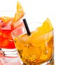 Detail of two cocktail with orange slice on top isolated on white background