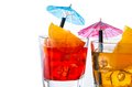 Detail of two cocktail with orange slice and umbrella on top isolated on white background