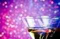 Detail of two glasses of cocktail on bar table blue and violet tint light bokeh background with space for text Royalty Free Stock Photo