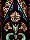 Detail of Victorian stained glass window showing white flower and decorative detail Royalty Free Stock Photo