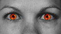 Detail view of female eyes with flames instead the iris Stock Image