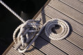 Detail yacht rope around cleat on jetty Royalty Free Stock Photography