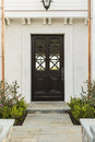 Detailed wooden front door of white brick home intricate design on a to a family features criss cross glass patterns house is Stock Photo