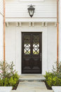 Detailed wooden front door of white brick home intricate design on a to a family features criss cross glass patterns house is Royalty Free Stock Photo