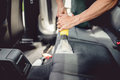 detailing and car care concept - Professional using steam vacuum for draining stains