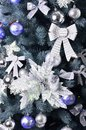 Details of a Christmas tree. Detail shot of Christmas tree branches hung with ribbons and Christmas toys. The concept of the trad