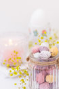 Details of festive Easter table setting, chocolate candy Easter eggs in pastel colors in crystal jar, candle, flowers Royalty Free Stock Photo