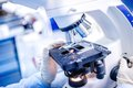 Details of medical laboratory, scientist hands using microscope for chemistry test samples Royalty Free Stock Photo