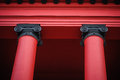 Details of two beautiful red columns supporting roof of old red building Royalty Free Stock Photo