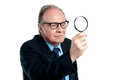 Detective  exploring through a magnifying glass Royalty Free Stock Images
