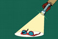 Detective flashlight beam shines on womens red sunglasses