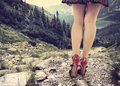Determination concept with a woman trying to climb down a mountain in elegant shoes Royalty Free Stock Image