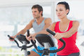 Determined couple working out at spinning class in gym young a bright Stock Image