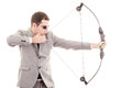 Determined handsome businessman aiming at target with bow this image has attached release Royalty Free Stock Photo