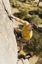 Determined man climbing rock full length of men Stock Photography