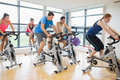 Determined people working out at spinning class five in gym Royalty Free Stock Photo