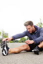 Determined runner in the middle of stretch for workout routine portrait Royalty Free Stock Photo