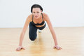 Determined sporty woman doing push ups in fitness studio portrait of a beautiful Stock Image