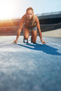 Determined sprinter at starting block young woman in the starter position on a race track a sports stadium looking up camera with Stock Photography
