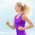 Determined woman runner jogging and running young at beach fit blond female is wearing purple tank top jogger is exercising during Royalty Free Stock Photos