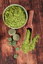 Detox chlorella spirulina and wheatgrass ground and pills with wooden spoon on brown wooden background top view alternative Stock Photography