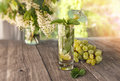 Detox water mint, grape juice and ice in a glass on a background of a bouquet of cherry and grapes in a Sunny day. The horizontal