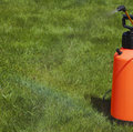 Device of spraying pesticide at the sunshine produces a rainbow over green grass Royalty Free Stock Images