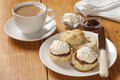 Devon cream tea scones jam and a cup of on an old pine table Royalty Free Stock Photography