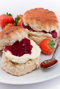 Devonshire cream tea traditional afternoon of scones topped with clotted and strawberry jam often served with coffee or Royalty Free Stock Image