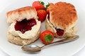 Devonshire cream tea traditional afternoon of scones topped with clotted and strawberry jam often served with coffee or Royalty Free Stock Photography