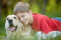 Devoted friends portrait of happy lad with his friendly pet lying on green grass Stock Photo
