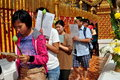 Devout thais carrying prayer cards and lotus flower buds in procession around the sacred golden chedi at wat doi suthep in chiang Stock Photos