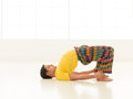 Dhanurasana pose colorful dressed male repeating yoga exercises in a white room with window background Stock Image