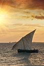 Dhow traditional sailing vessel at sunrise sunset a african with full sail to the wind on a golden background of qcean and warm Stock Image